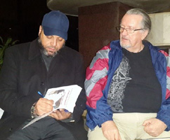 Abu autographs a copy of his book for me.